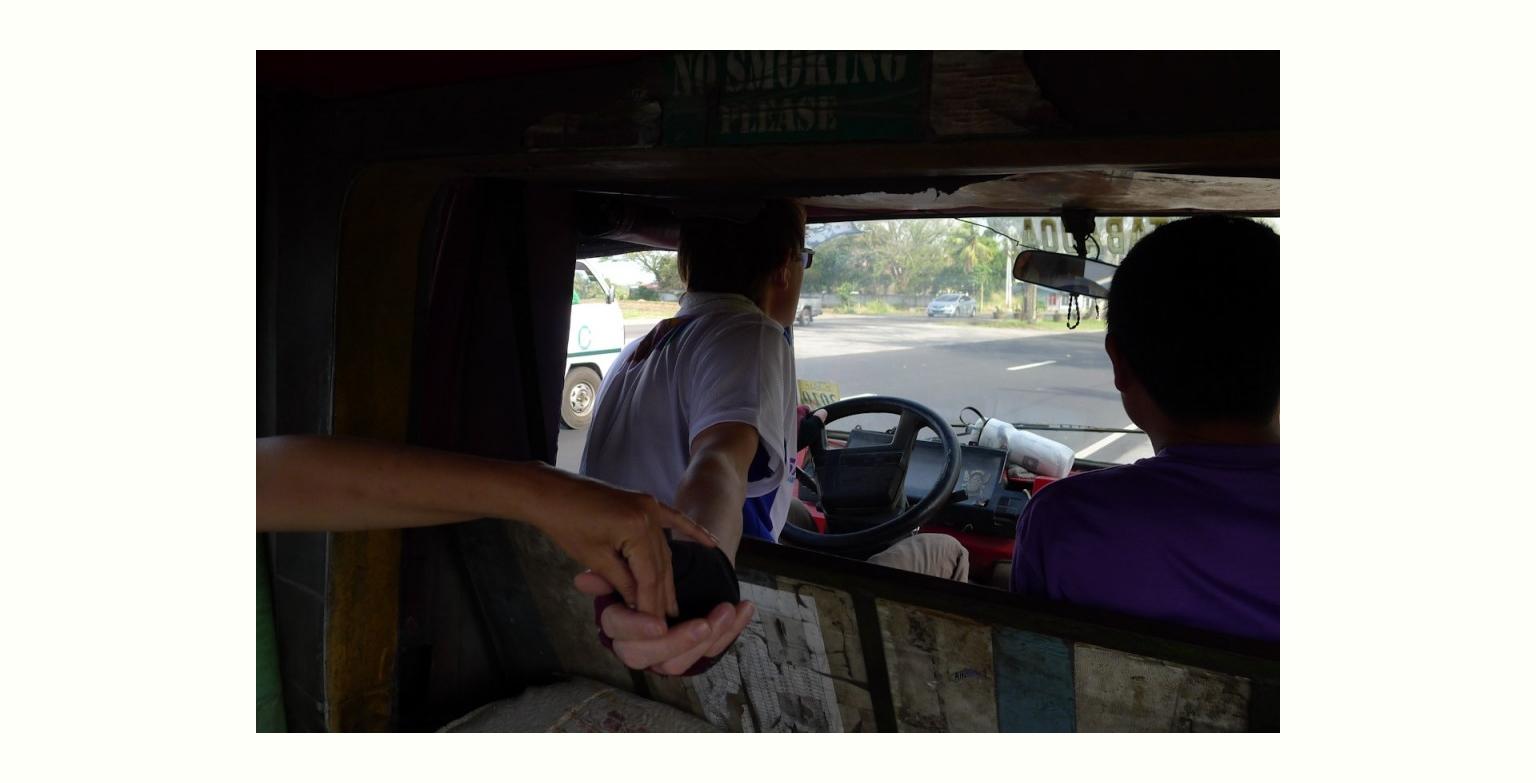 運賃の受け渡しをするジープの乗客とドライバー (inside Jeepney)